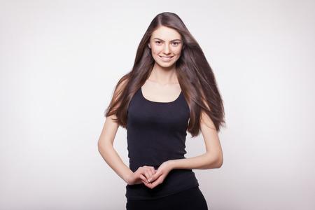 plan éloigné: instantané de modèle de cheveux longs souriante en studio Banque d'images