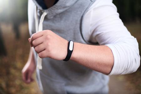 trainer device: Closeup of fitness bracelet during park jog Stock Photo