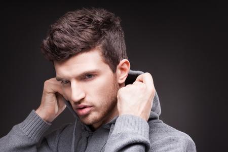 Stijlvolle man in hoodie op zwarte achtergrond Stockfoto