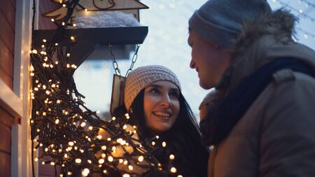 couple outdoor: Young couple have fun with christmas lights during walks on christmas market