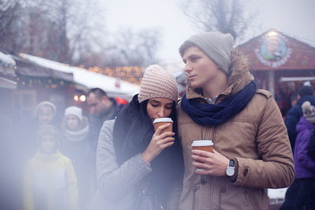 Couple drinking hot beverage during walk by Christmas market Reklamní fotografie