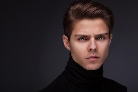 volto uomo: Elegante ragazzo vicino ritratto su sfondo nero Archivio Fotografico
