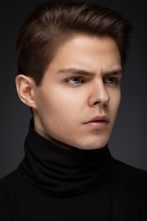 Stylish guy close up portrait on black background