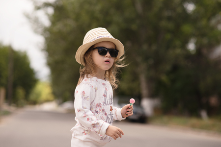 girl in a hat: Portrait of stylish little girl in hat and sunglasses with lollipop