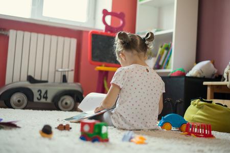 Kleines Mädchen liest Buch im Kinderzimmer Standard-Bild - 64924138
