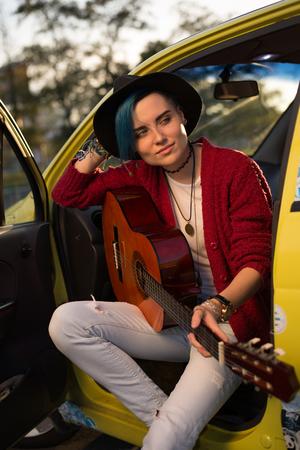 Woman guitarist playing music outdoors Reklamní fotografie