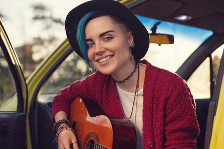 subculture: Closeup face portrait of folk singer with guitar in car outdoors