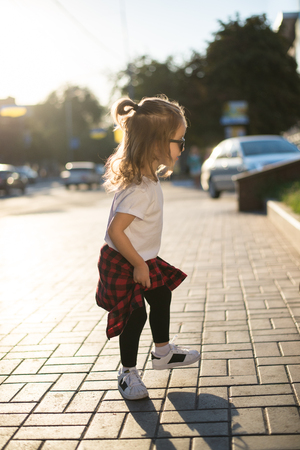 Stylish funny hipster little girl on street