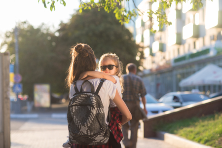Hipster style mother and daughter walks in city street