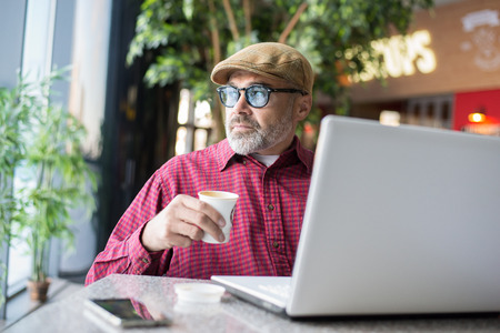 Adult Hipster man using computer in public place