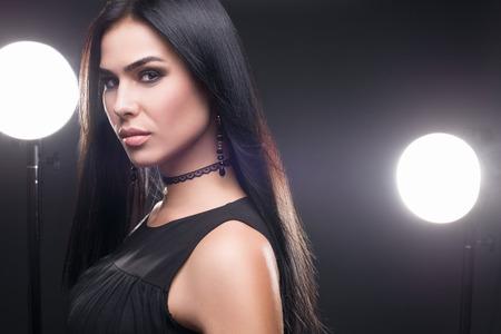 Beauty shot of brunette luxury model in dark dress and jewelry on dark background Reklamní fotografie