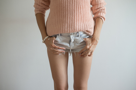 closeup of street style posing girl in short jeans shorts and pink pullover