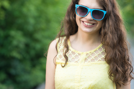 closeup face portrait of happy young woman during summer walk
