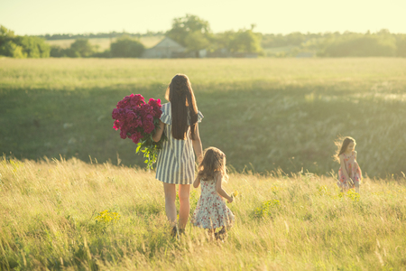 family portrait of mother with two daughters during nature stroll Stok Fotoğraf