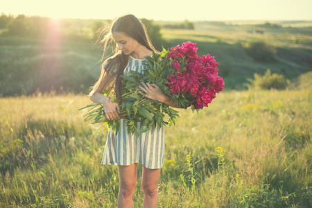 portrait of woman with big bouquet of red peonies outdoors Stockfoto
