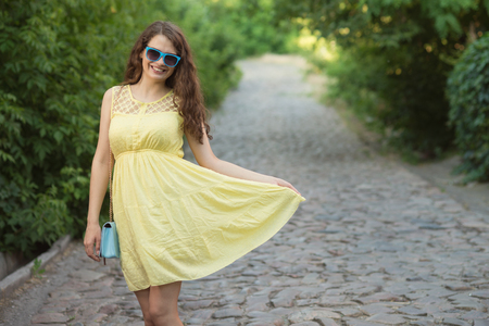 Young lady dancing on street in yellow dress and blue bag and eyeglasses