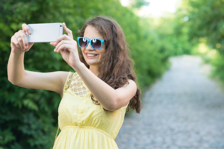 Young lady using smartphone camera to take selfie outdoors