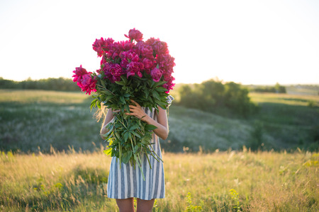 spectacular portrait of woman with big bouquet of rose peonies at sunset