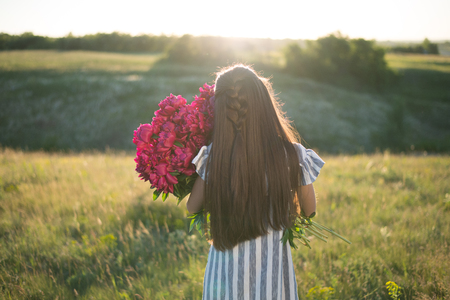 portrait of woman with big bouquet of red peonies outdoors photo