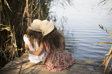 Little sisters are sitting on the shore of the lake. Childhood friendship Stockfoto