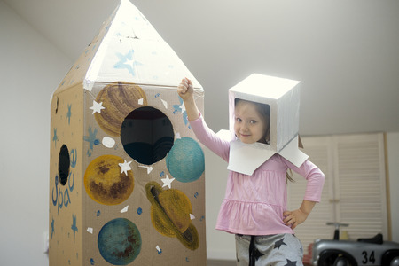Little astronaut ready to travel to the stars. Playing with spaceship