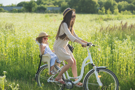 Mother and daughter have bike ride on nature. Summertime activity Stockfoto