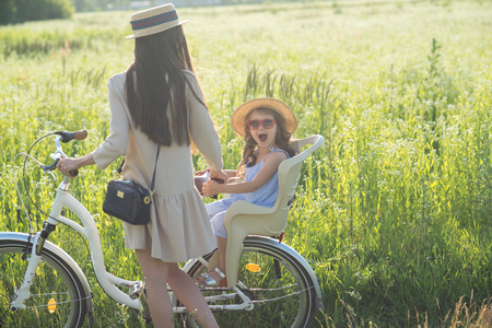 Mother and daughter have bike ride on nature. Summertime activity Reklamní fotografie