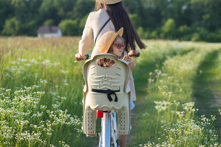 Mother and daughter have bike ride on nature. Summertime activity Standard-Bild - 109152138