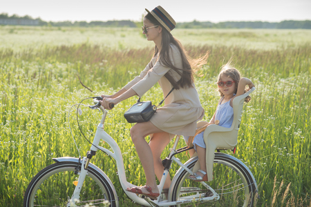 Mother and daughter have bike ride on nature. Summertime activity Standard-Bild - 109152139