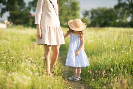Stylish young mother with toddler girl walking on nature Standard-Bild - 103851901