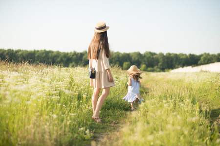 Stylish young mother with toddler girl walking on nature