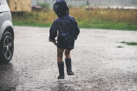 Little girl playing alone outside in bad weather. Summer rain Reklamní fotografie - 104518453