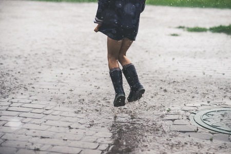 Little girl playing alone outside in bad weather. Summer rain