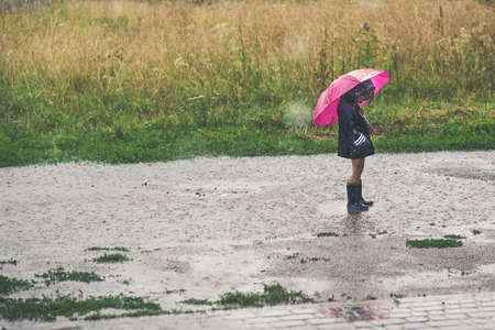Little girl playing alone outside in bad weather. Summer rain Standard-Bild - 104517835
