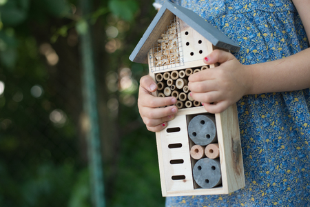 Green schooling. Girl holding insect hotel Standard-Bild - 109152233