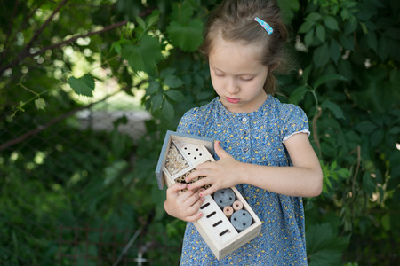 Green schooling. Girl holding insect hotel Standard-Bild - 109152234