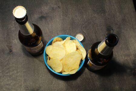 horizontal format: Two beer bottles, bowl of chips, wood surface. Horizontal format. The bottle is without label.