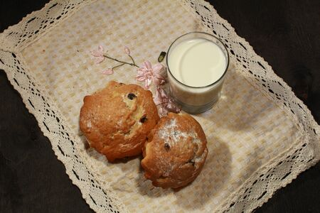 choco chips: Homemade muffins and glass of milk on wooden background