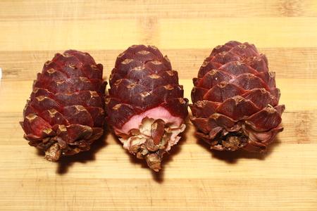 cone shell: three cedar cone on white wood background Stock Photo