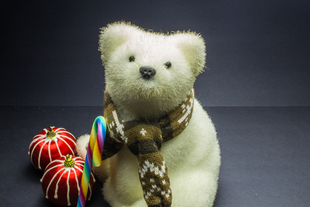 White polar bear toy with candy and two stripes Christmas balls on black background Stock Photo