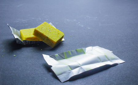 Dehydrated bouillon stock cube salty meat and vegetables aromatic yellow spice, ingredient single whole condiment portion wrapped, open in paper pack Stock Photo