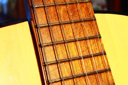 Wooden yellow acoustic guitar with metal strings close up
