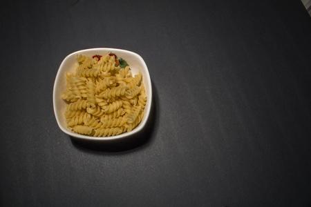 rotini: macaroni pasta in plate on black background Stock Photo