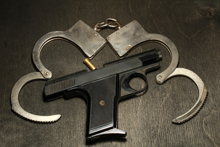 gun and handcuffs on black wooden background Stock Photo