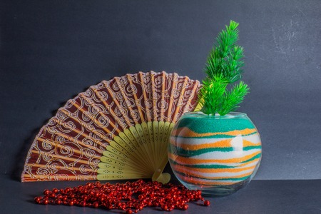 Chinese fan, vase with colored sand and spruce branch on the dark background Stock Photo