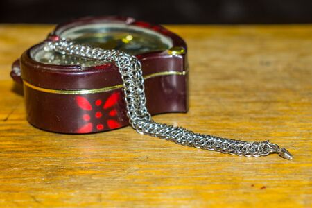 plastic box with a steel bracelet on dark wooden background