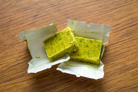 Dehydrated bouillon stock cube salty meat and vegetables aromatic yellow spice, ingredient single whole condiment portion wrapped, open in paper pack on wooden background