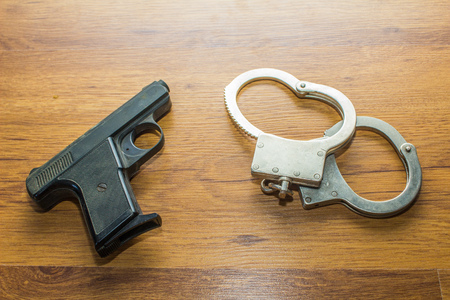 handcuffs: gun and handcuffs on wooden background Stock Photo