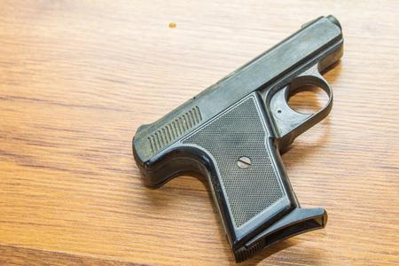 black handgun on wooden background
