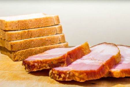 Raw smoked bacon slices with bread on wooden board Reklamní fotografie